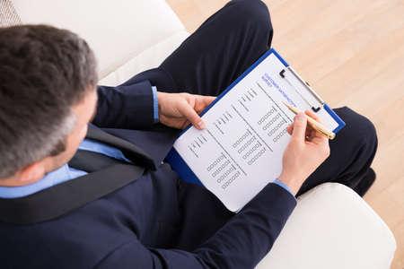 소파에 앉아 사업가의 높은 각도보기 고객 설문 양식을 작성