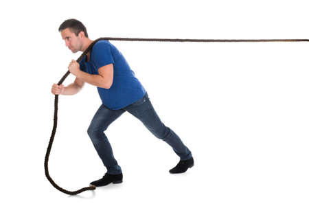 pulling rope: Portrait Of A Man Pulling Rope Over White Background Stock Photo
