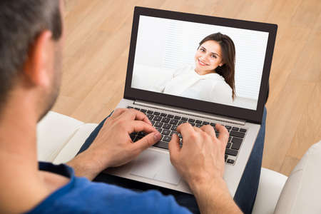 Man Having A Videochat With Woman On Laptop Stock Photo