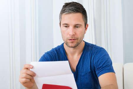 preocupacion: Retrato De Infeliz hombre sentado en el sofá de leer la carta