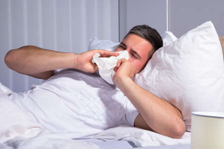 Man Infected With Cold And Flu Blowing His Nose In Tissue Paper Stock Photo