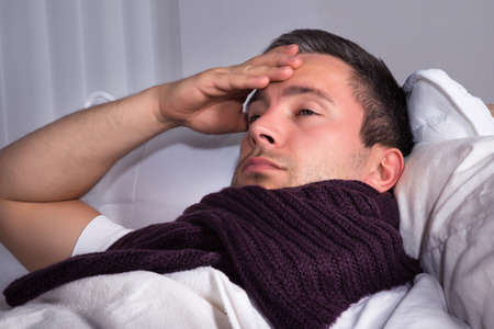 Man With Woolen Scarf Around His Neck Suffering From Cold And Fever photo