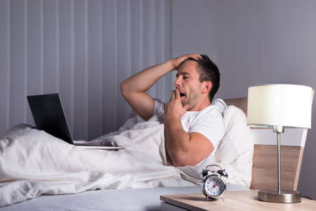 tired person: Portrait Of A Sleepy Man Yawning On Bed Looking At Laptop