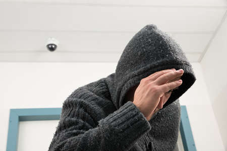 Man In Hooded Sweatshirt Trying To Hide From Security Camera Stock Photo