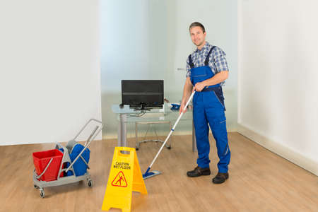 brooms: Portrait Of A Male Janitor Cleaning Office With Mop And Wet Floor Sign Stock Photo