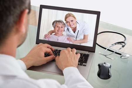 video conference: Doctor Having Video Conference With Senior Patient And Nurse