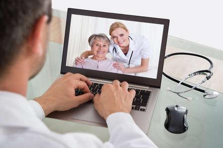 paciente: Doctor que tiene Videoconferencia con el paciente mayor y enfermera