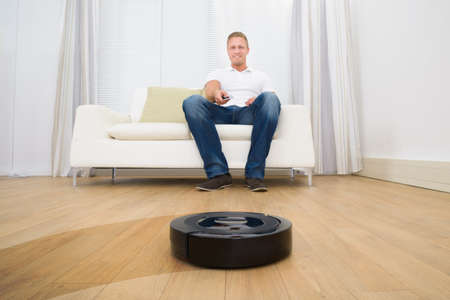cleaner: Happy Man Operating Robotic Vacuum Cleaner With Remote Control At Home
