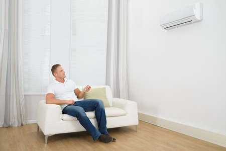 Man Sitting On Sofa Operating Air Conditioner With Remote Controller