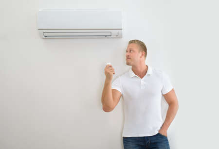 cold air: Portrait Of A Man Operating Air Conditioner With Remote Controller Stock Photo