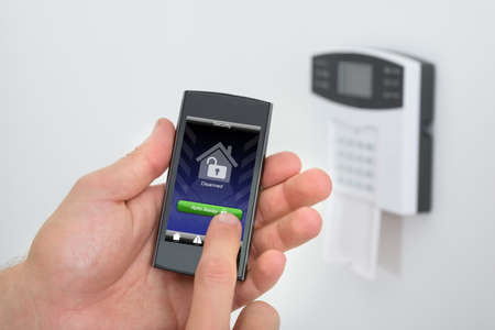 Security Alarm Keypad With Person Arming The System With Remote Controller photo