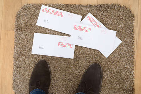 Close-up Of Persons Feet And Important Letters On Doormat