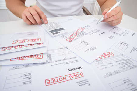 unpaid: Close-up Of A Man Calculating Unpaid Bills Using Calculator