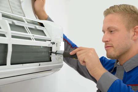 Portrait Of Young Male Technician Repairing Air Conditioner Stock Photo
