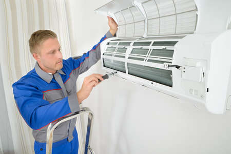 Young Man Repairing Air Conditioner Standing On Stepladder Фото со стока