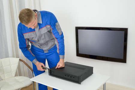technician: Portrait Of Young Male Technician Repairing Amplifier