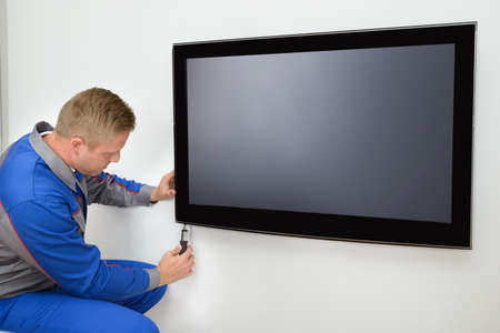 lcd display: Portrait Of Young Male Technician Repairing Television
