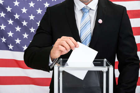 plebiscite: Person In Front American Flag Putting Ballot In Glass Box