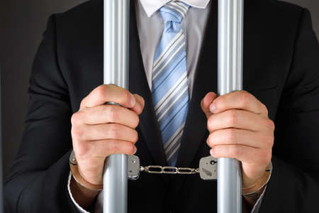 Close-up Of Handcuffed Businessman In Jail Holding Metal Bars 스톡 콘텐츠