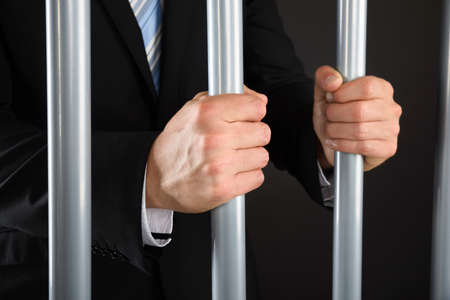 metal bars: Close-up Of Businessman Hand Holding Metal Bars In Jail Stock Photo