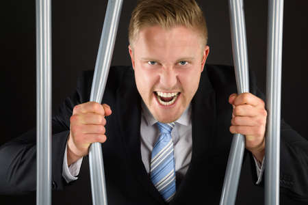 prison break: Portrait Of Aggressive Businessman In Jail Bending Bars