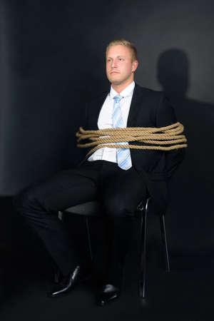 gefesselt: Portrait der jungen Geschäftsmann gebunden mit Seil an einen Stuhl