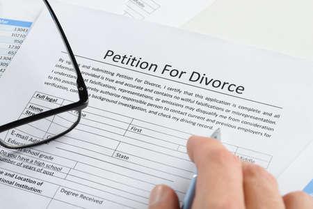 離婚届の嘆願書にペンを持つ手のクローズ アップ 写真素材
