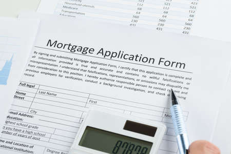 mortgage application: Pen And Calculator On Mortgage Application Form