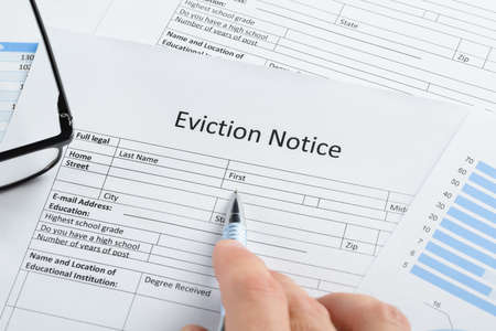 evicted: Close-up Of Hand With Pen And Eyeglasses Over Eviction Notice Paper