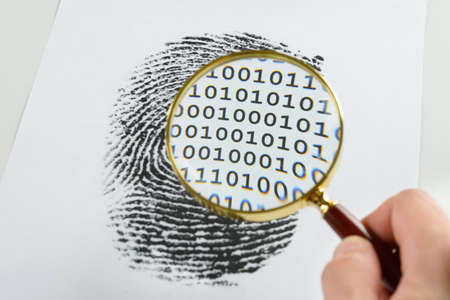 Person Hand With Magnifying Glass Over A Finger Print Revealing Binary Code Within The Print
