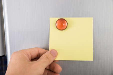 Primer plano de la mano de la persona holding en blanco nota amarillo pegadas sobre Nevera Puerta