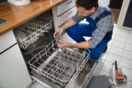 man machine: Portrait Of Male Technician Repairing Dishwasher In Kitchen