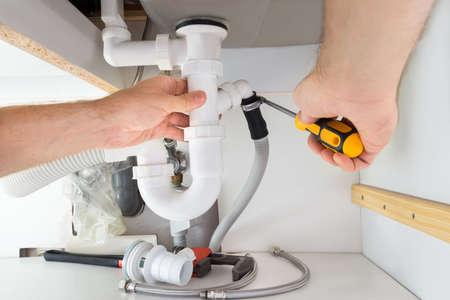 bathroom equipment: Close-up Of A Male Plumber Repairing Sink In Bathroom