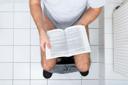 urinating: High Angle View Of A Man In Toilet Reading Book