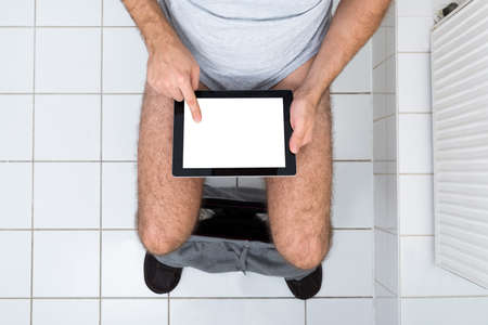 a toilet seat: High Angle View Of A Man In Toilet Using Digital Tablet Stock Photo
