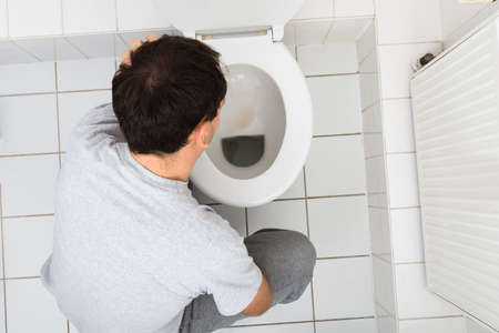 toilet bowl: High Angle View Of A Man Vomiting In Commode