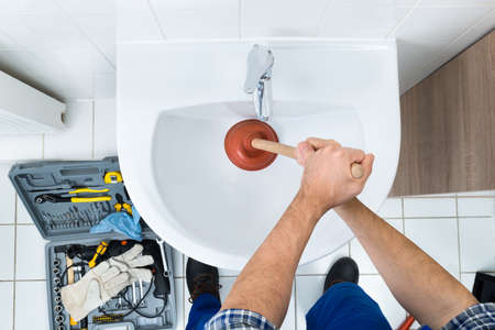 sink drain: High Angle View Of Male Plumber Using Plunger In Bathroom Sink