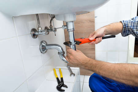 plumbing: Close-up Of Male Plumber Fixing Sink In Bathroom