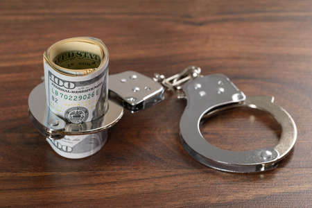 drug bust: Close-up Of Rolled Up Dollar Bills With Handcuffs Stock Photo