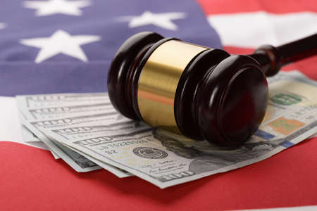 Close-up Of Wooden Brown Gavel On Usa Dollar Banknotes And American Flag photo