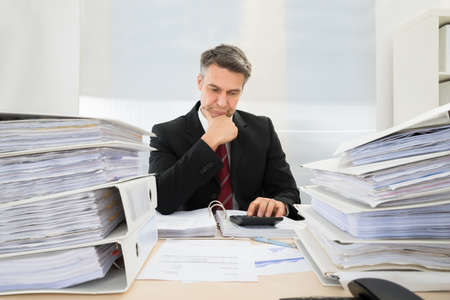 Photo Of Mature Businessman Calculating Invoices In Office