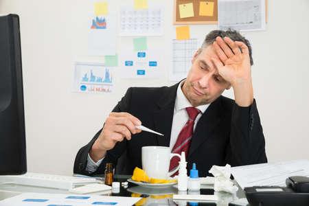 Enfermo del hombre de negocios maduro que sufre de fiebre Mirando a Termómetro Foto de archivo