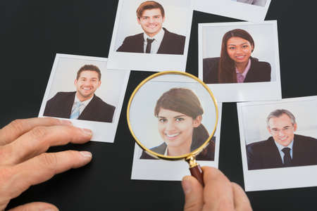 magnifying glass man: Businessman Looking At  Candidate Photograph Through Magnifying Glass