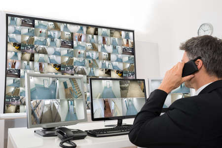 Security System Operator Looking At Cctv Footage While Talking On Telephone Archivio Fotografico