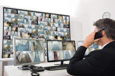 sicurezza sul lavoro: Security System Operator Guardare filmati CCTV mentre parla al telefono