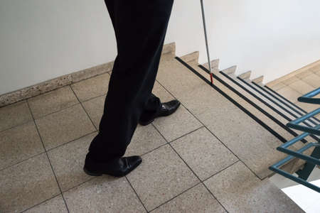 impaired: Close-up Of A Blind Man Walking Near Stairway Holding Stick