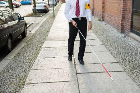 blind man: Blind Man Walking On Sidewalk Holding Stick Wearing Armband