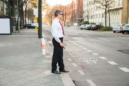 a blind: Portrait Of A Blind Mature Man Crossing Road Holding Stick Stock Photo