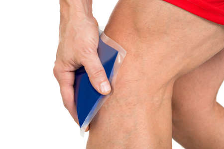 human knee: Close-up Of Hand Holding Ice Gel Pack On Painful Knee Stock Photo