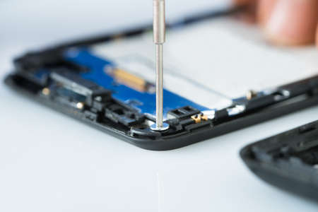 repair tools: Close-up Of Human Hand Repairing Cellphone With Screwdriver On Desk